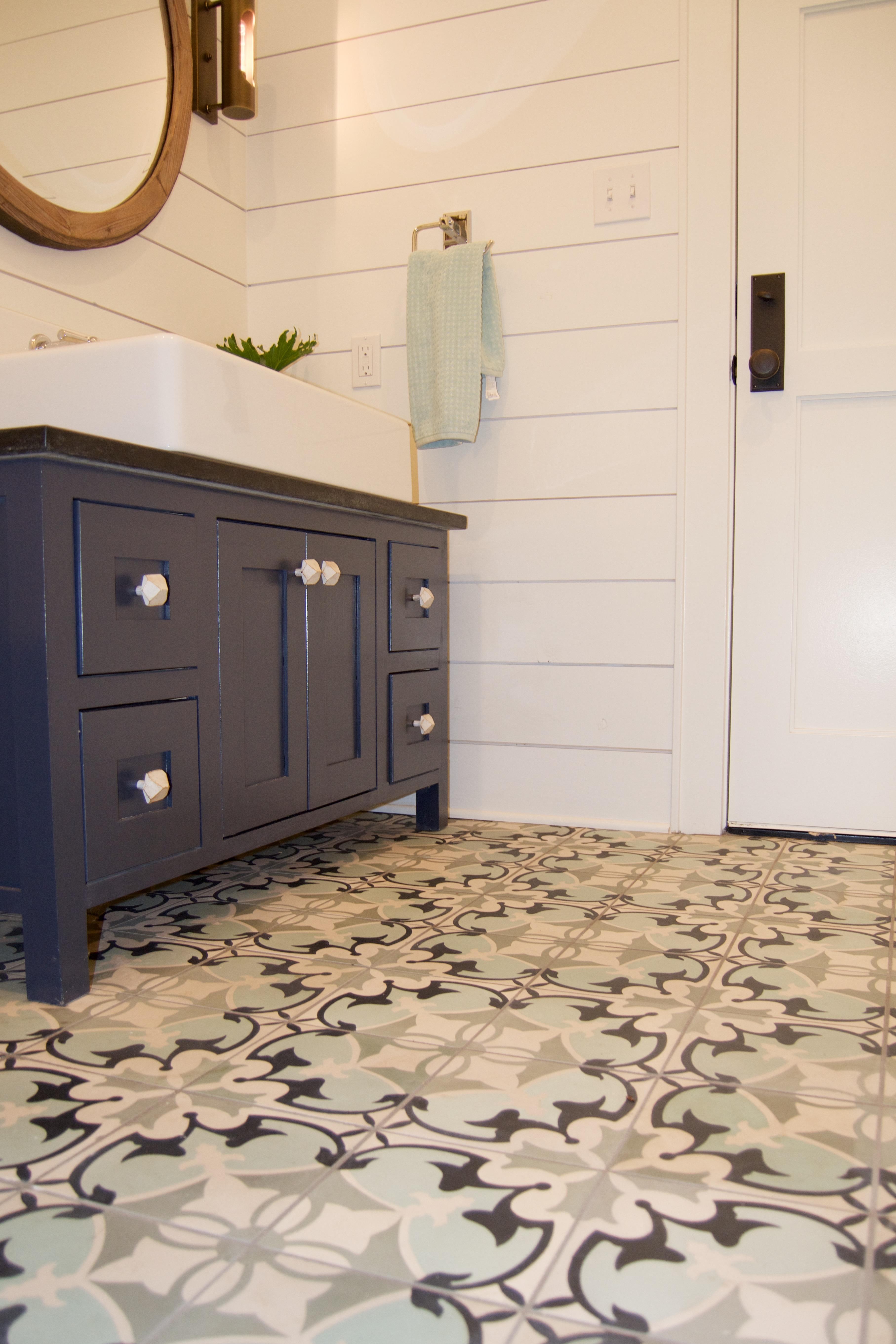 Cement tile floors patterned tile floor navy vanity shiplap round mirror