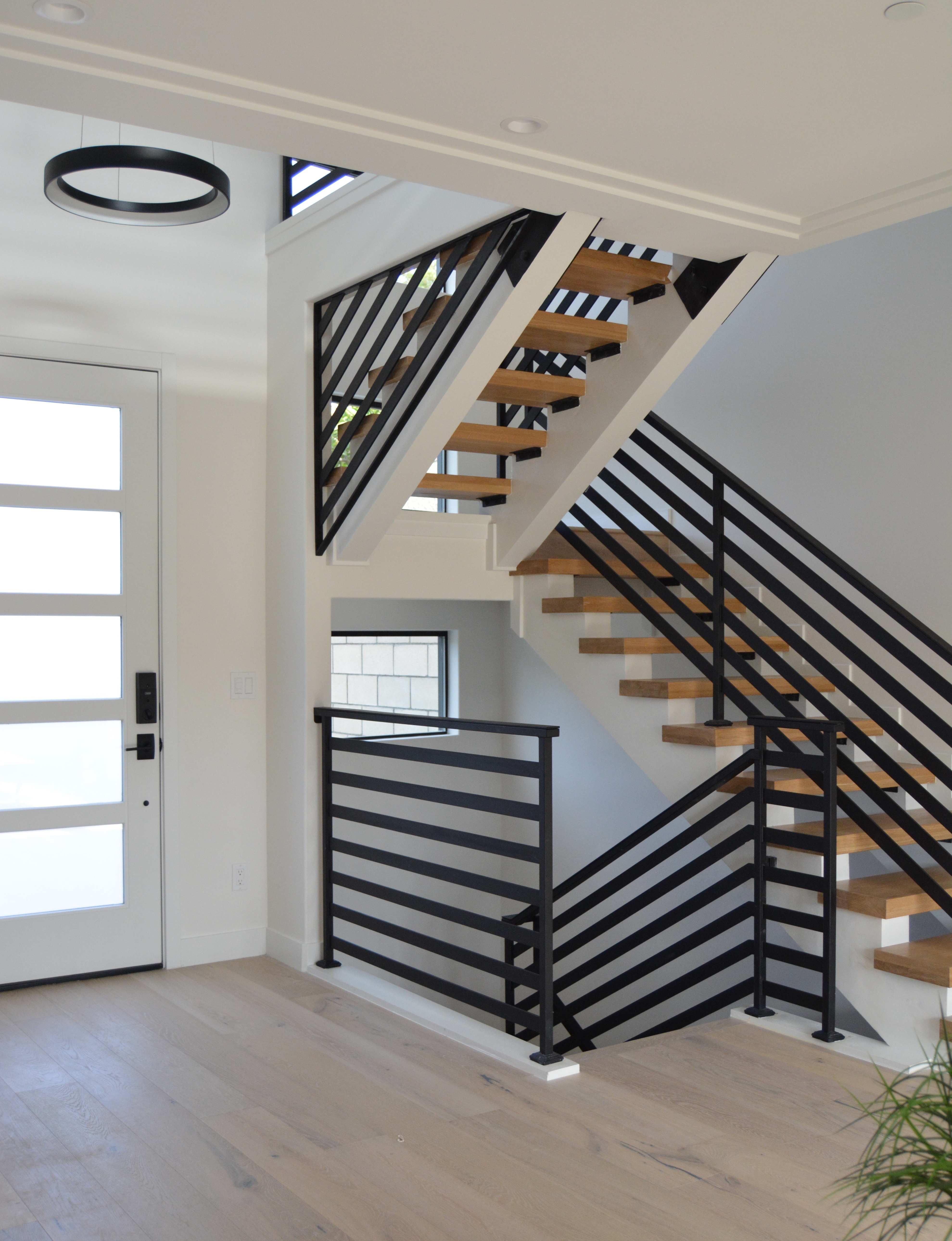 Dana Point Entry halo chandelier black steel railing