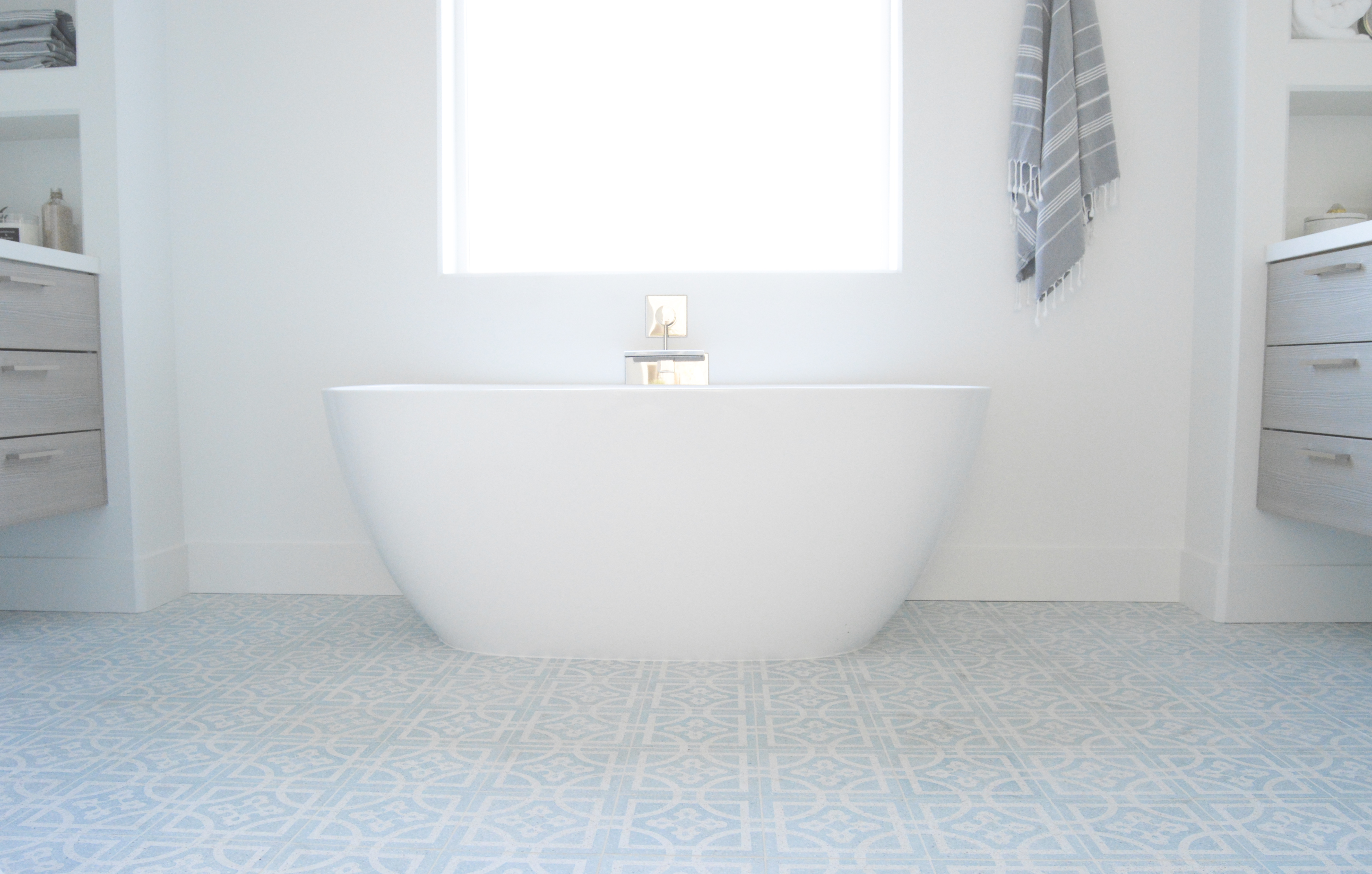 fish and arrow interiors janna parr blue patterned cement tile freestanding tub floating vanity built in shelving white blue and wood modern bathroom