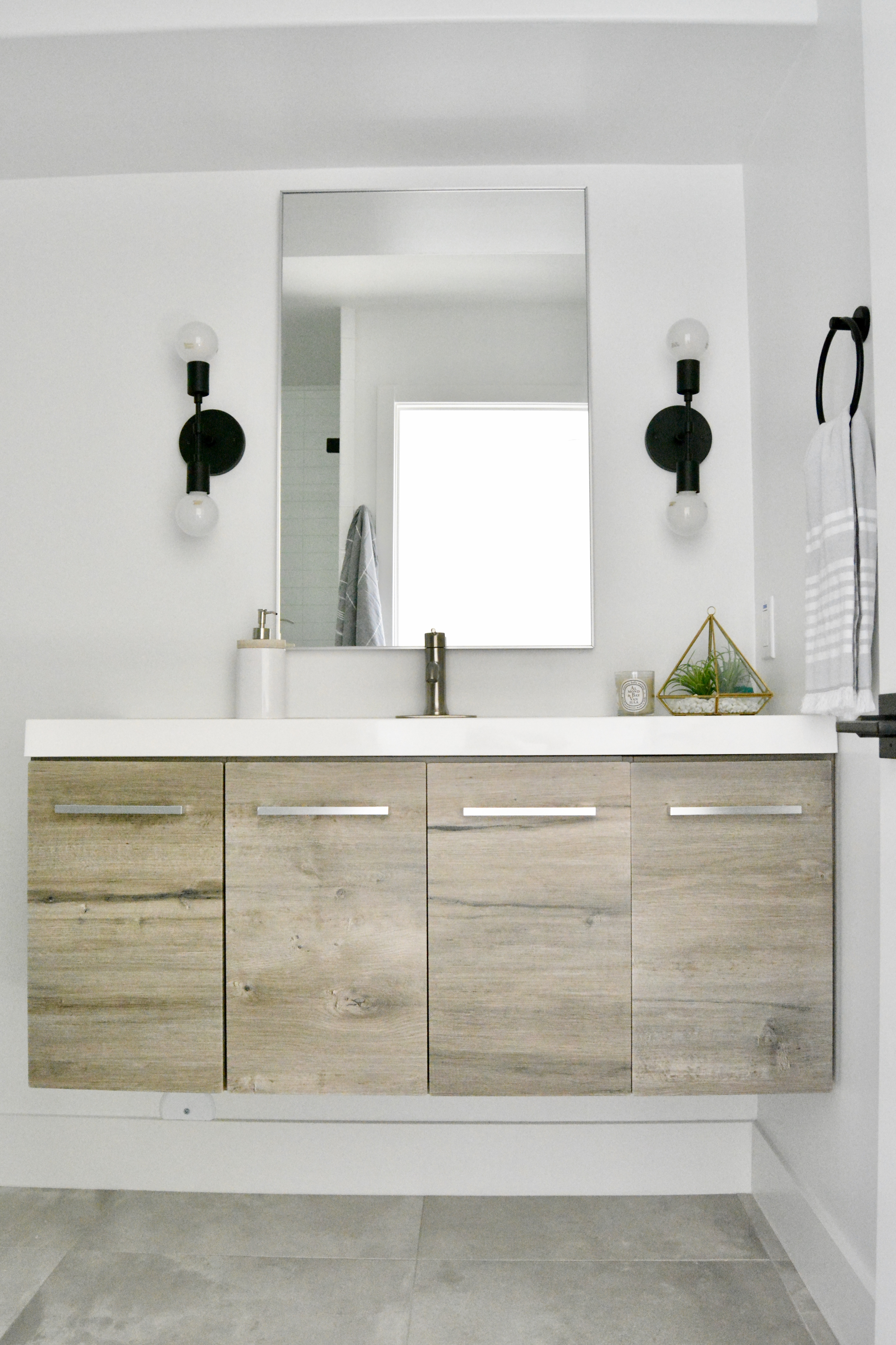 modern black white and wood bathroom mixed metals floating vanity fish and arrow interiors janna parr cedar and moss sconces