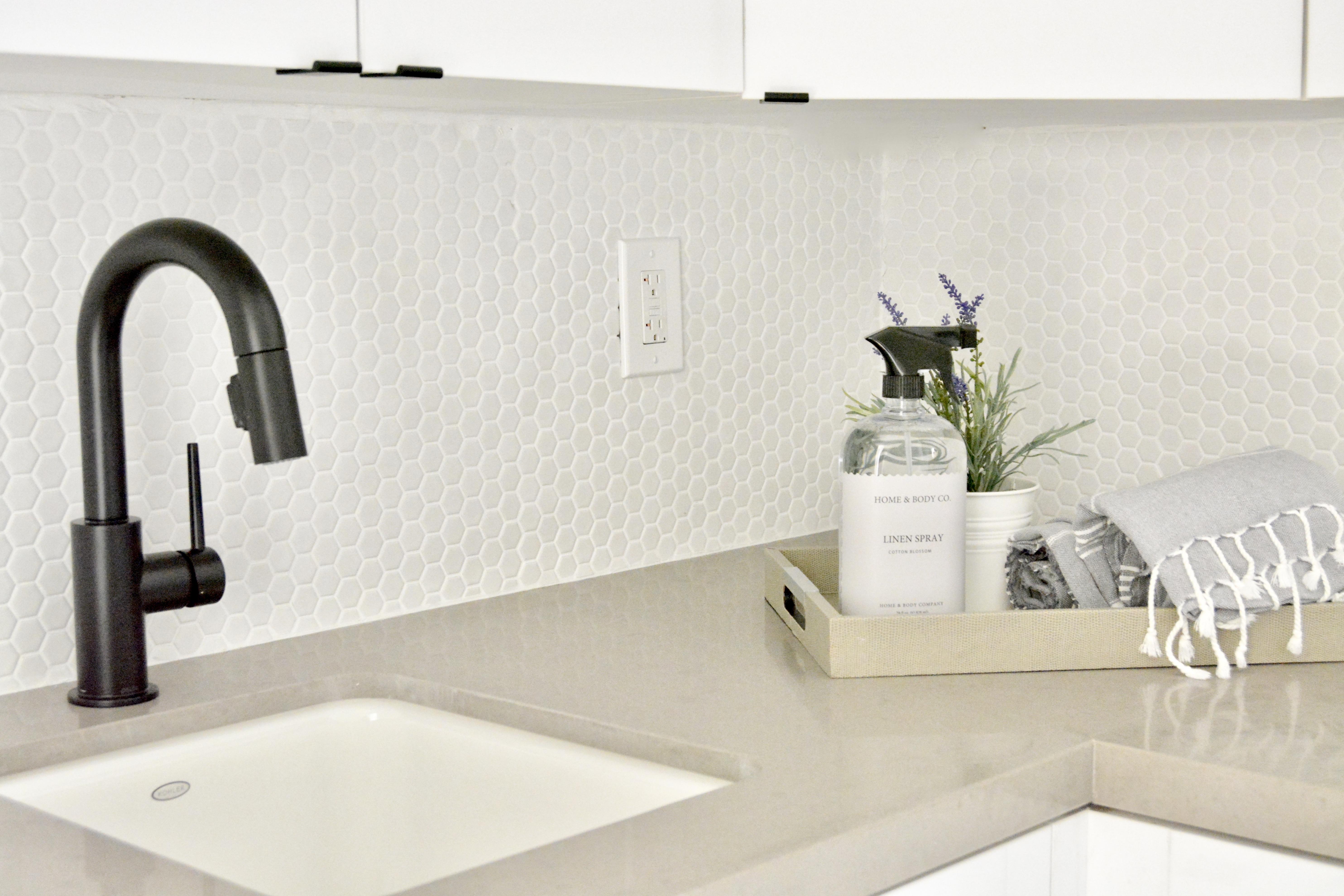 modern white laundry room black faucet gray quartz countertops black hardware fish and arrow interiors janna parr