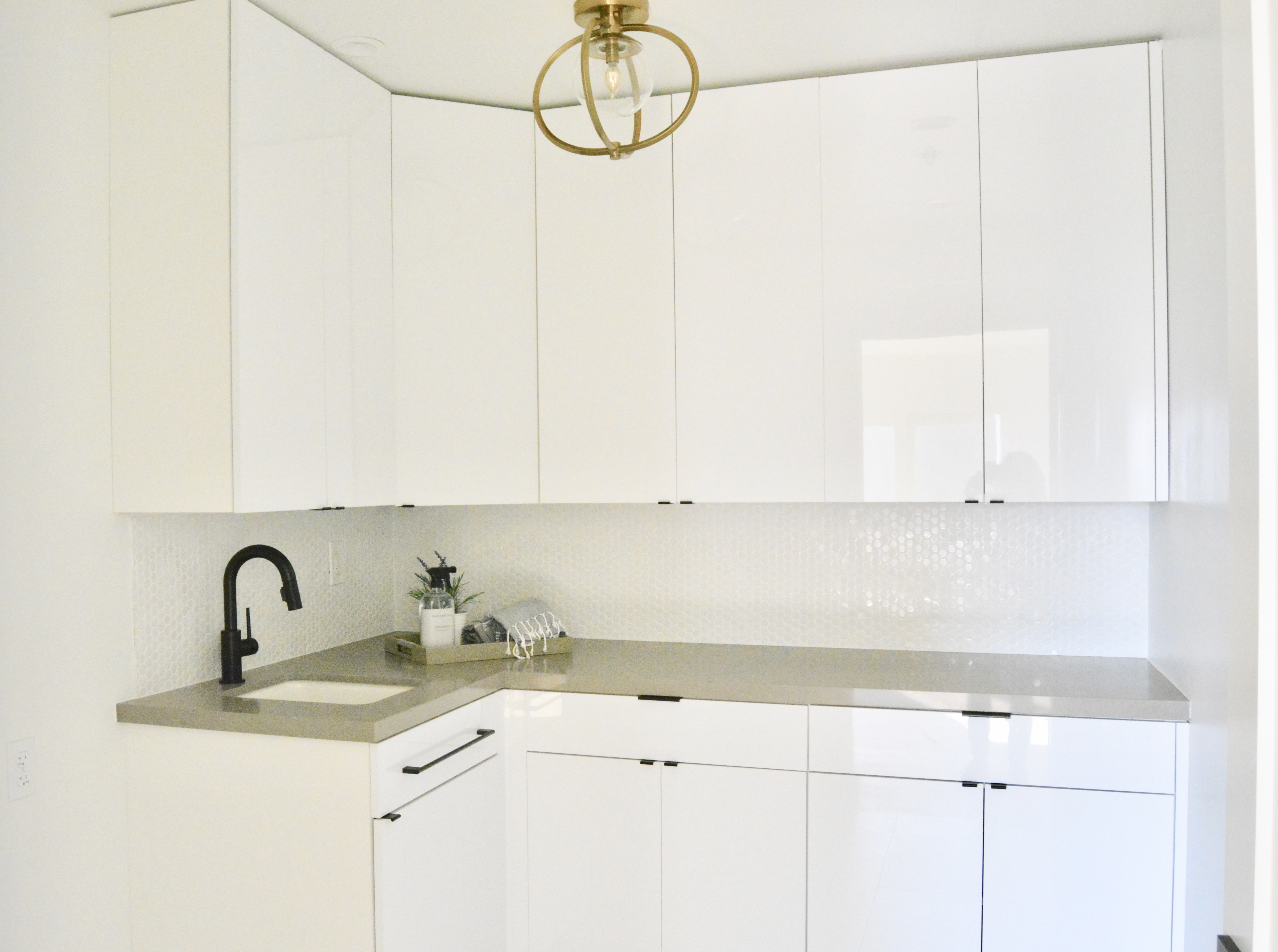 all white laundry room black and brass fixtures faucet and hardware gray quartz countertops fish and arrow interiors janna parr